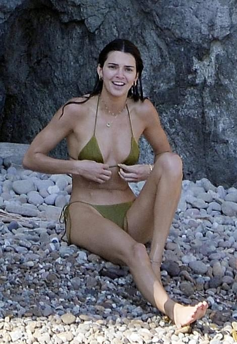 Kendall Jenner wearing a deep neck olive green bikini top with a halter neck and straps tied at the shoulder