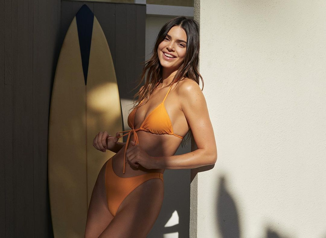 Kendall Jenner donning a plunging orange bikini top with spaghetti straps