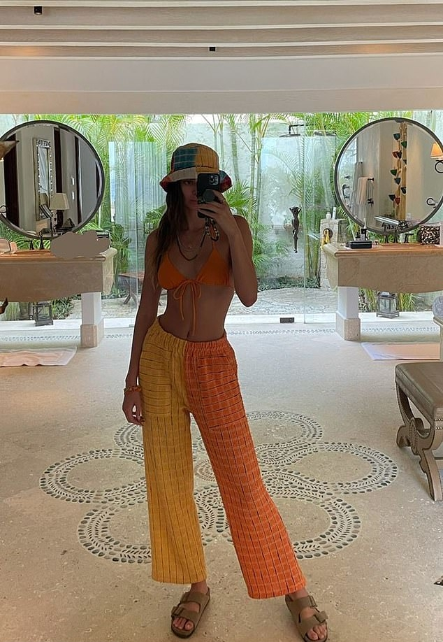 Kendall Jenner donning a fitted orange bikini top with a lace fabric