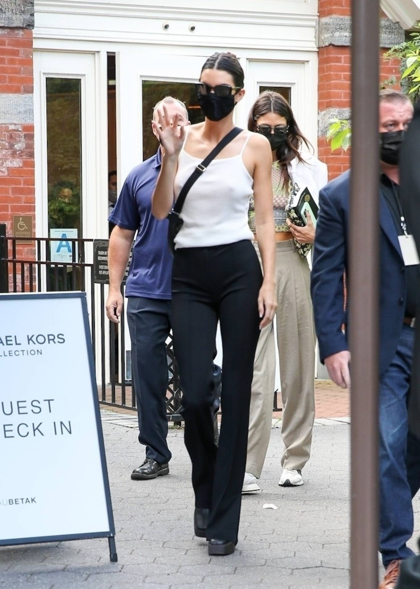 Kendall Jenner donning straight fit black split hem flare trousers with high rise