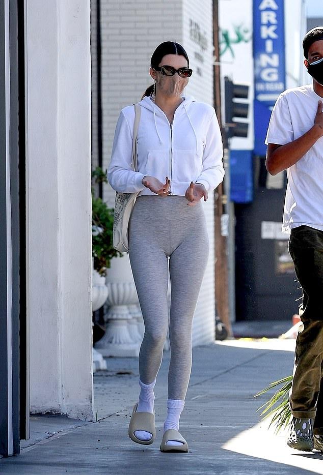 Kendall Jenner wearing white Yeezy open toe slippers