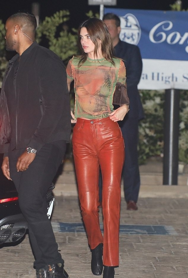 Kendall Jenner donning narrow black leather boots with high block heel