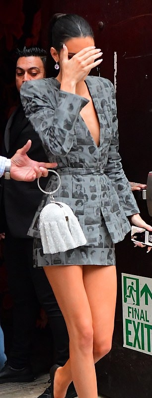 Kendall Jenner wearing a Close fitting grey printed blazer with full sleeves, padded shoulder, peak lapel collar, faces newsprint and cinched waist