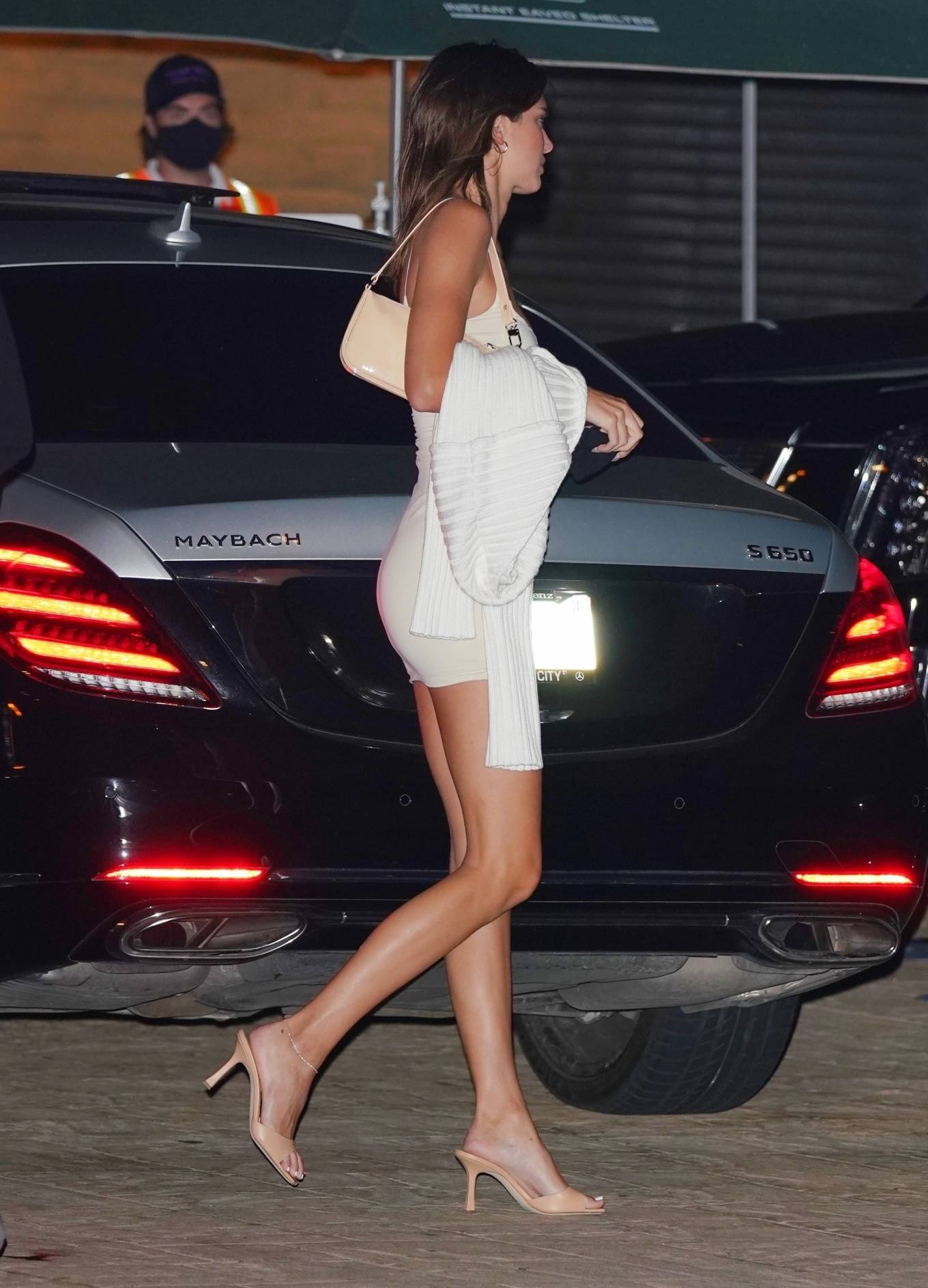 Kendall Jenner wearing a figure hugging white dress with a scoop neck and spaghetti straps