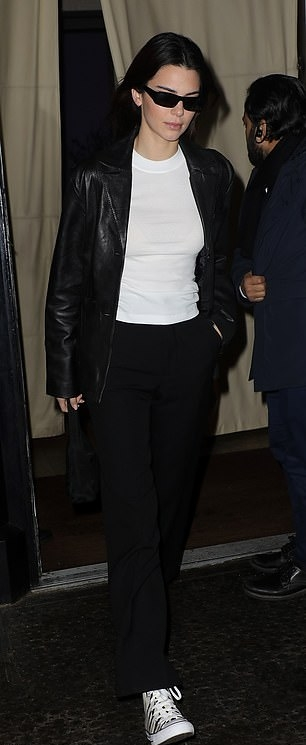 Kendall Jenner, black jacket, leather, white canvas shoes, white tee, relaxed fit, front zip, hip length, full sleeves, peak lapel collar, black Prada purse, black pants, black sunglasses. Kendall Jenner donning a relaxed fit black leather jacket with full sleeves and peak lapel collar