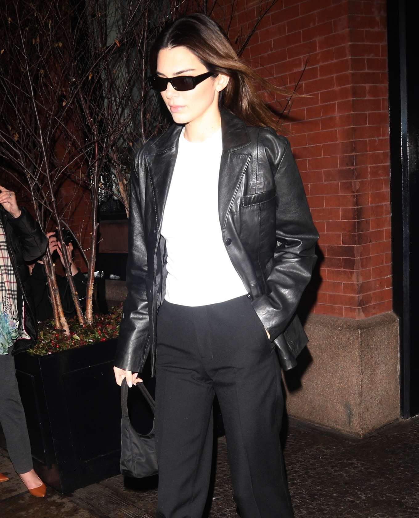 Kendall Jenner, black jacket, leather, white canvas shoes, white tee, front zip, hip length, full sleeves, peak lapel collar, relaxed fit, black Prada purse, black pants, black sunglasses. Kendall Jenner donning a relaxed fit black leather jacket with full sleeves and peak lapel collar