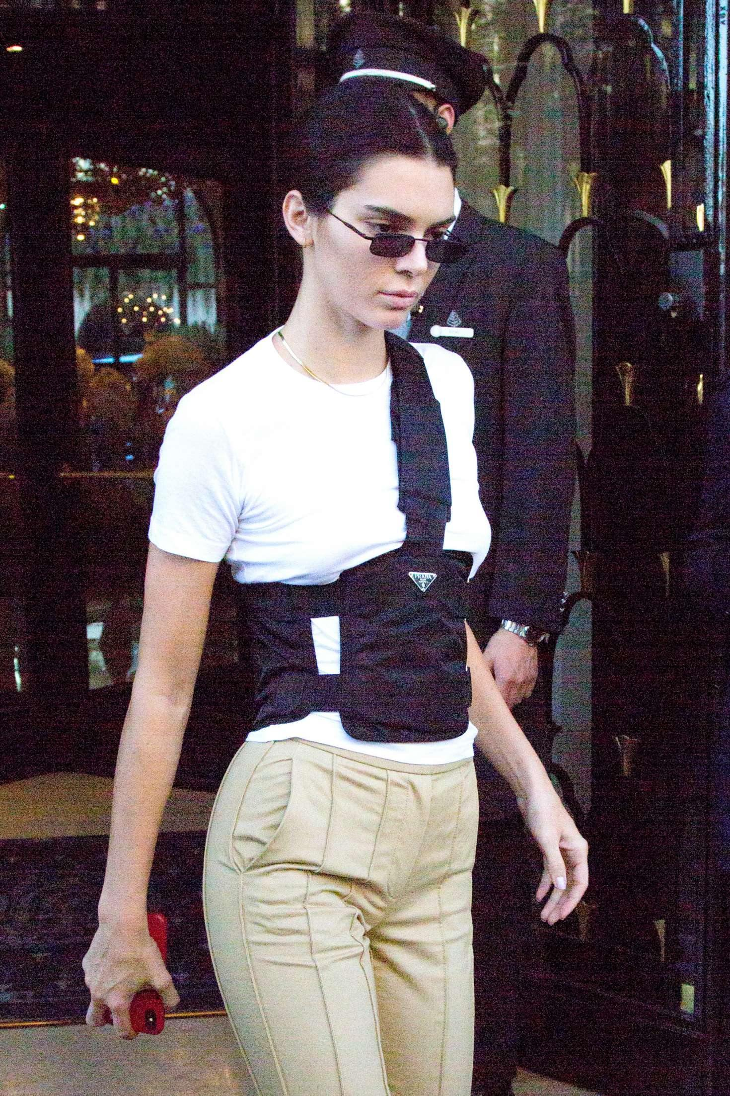 Kendall Jenner wearing pleated camel leather trousers with high rise with side pockets
