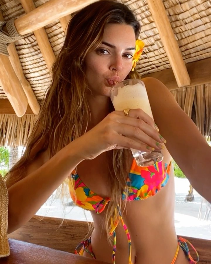 Kendall Jenner donning a Plunging yellow bikini top with floral print and spaghetti straps