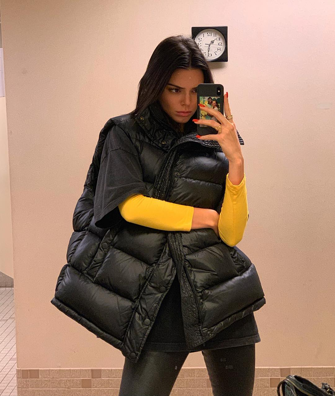 Kendall Jenner wearing a relaxed fit black puffer jacket with side pockets