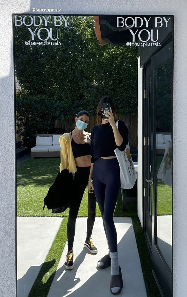 Kendall Jenner wearing chunky grey Yeezy slip on slide on sandal with rigged sole