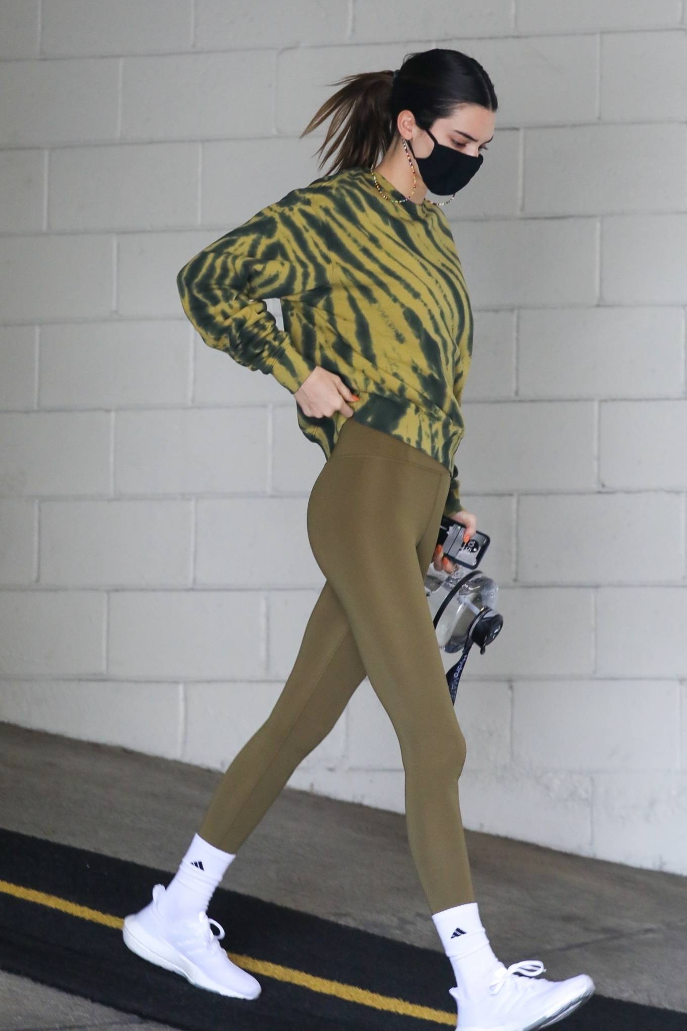 Kendall Jenner wearing a oversized golden sweatshirt with a cotton material, extra long sleeves and a crew neck