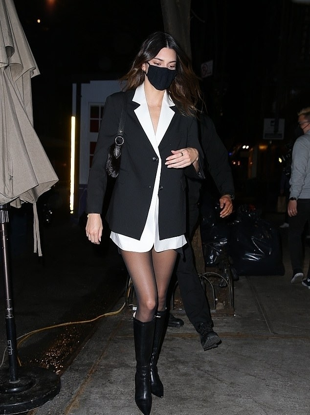Kendall Jenner donning sharp black leather knee high boots with high heel
