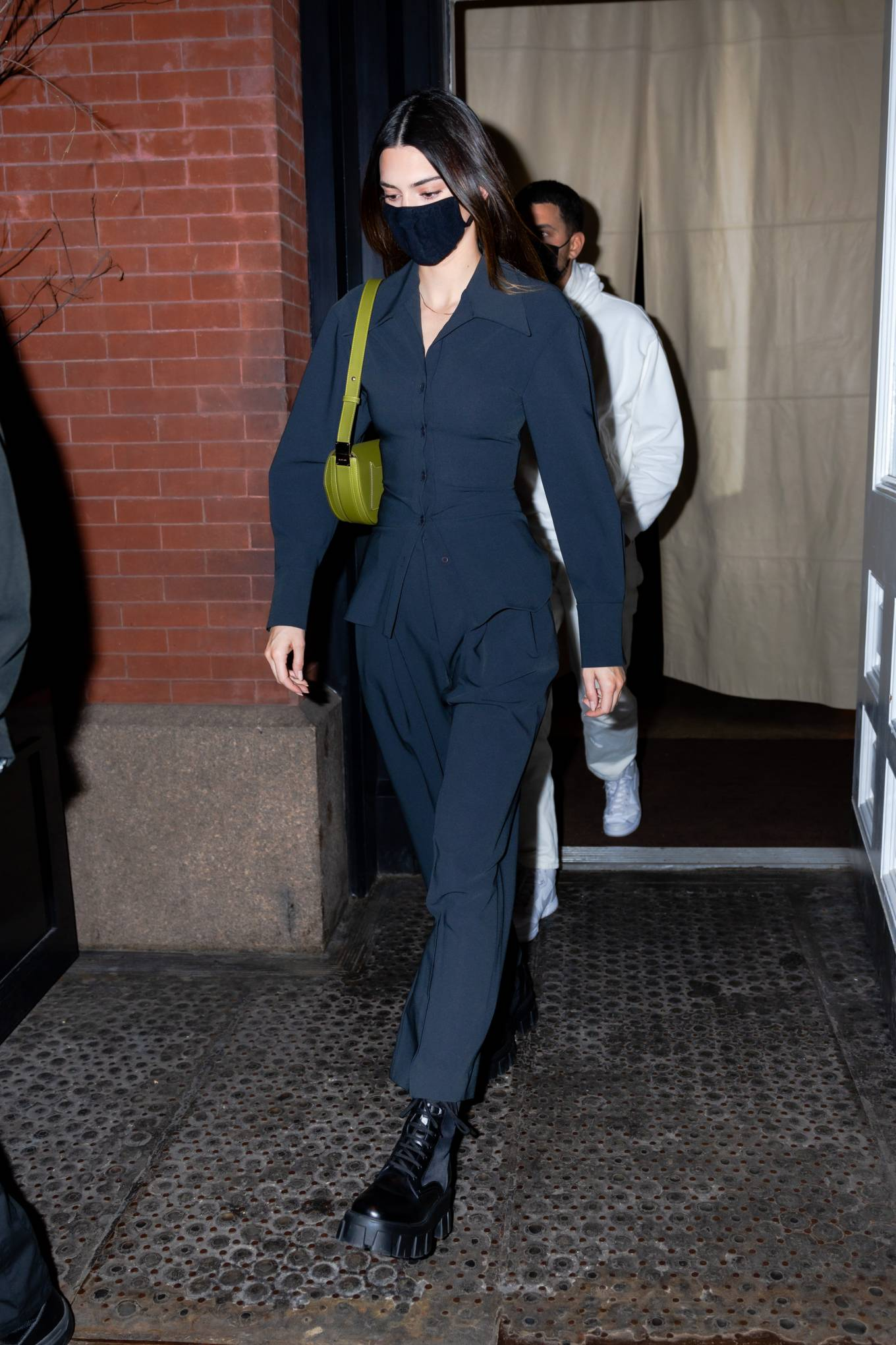 Kendall Jenner donning round black Prada lace-up combat boots with platform heels and attached removable mini bag