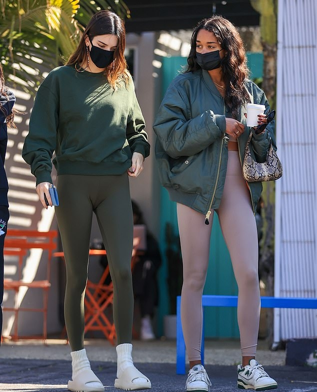 Kendall Jenner wearing figure hugging olive green high waist skinny workout leggings with brand logo