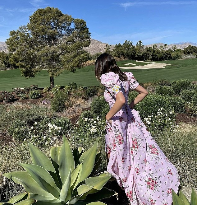 Kendall Jenner wearing a flattering baby pink dress with a silk fabric, bell sleeves, back zip, floral print and a V-neck