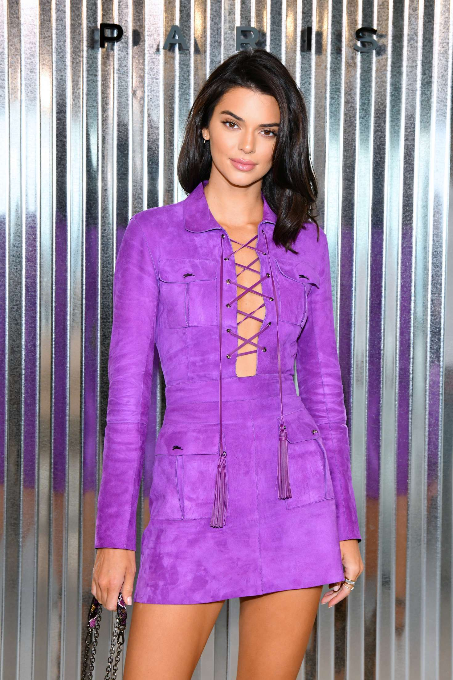 Kendall Jenner wearing a purple Long Champs dress with a suede material, full sleeves, shirt collar and cut out panel from neck down to the stomach which is tied through criss cross lace