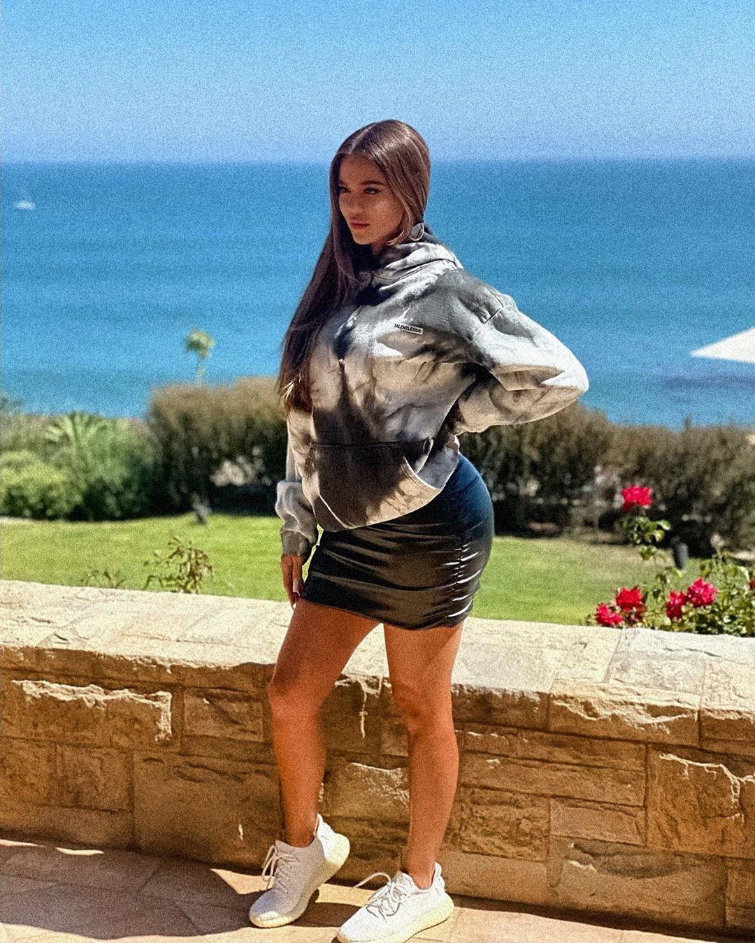 Khloe Kardashian donning a black skinny draped mini skirt