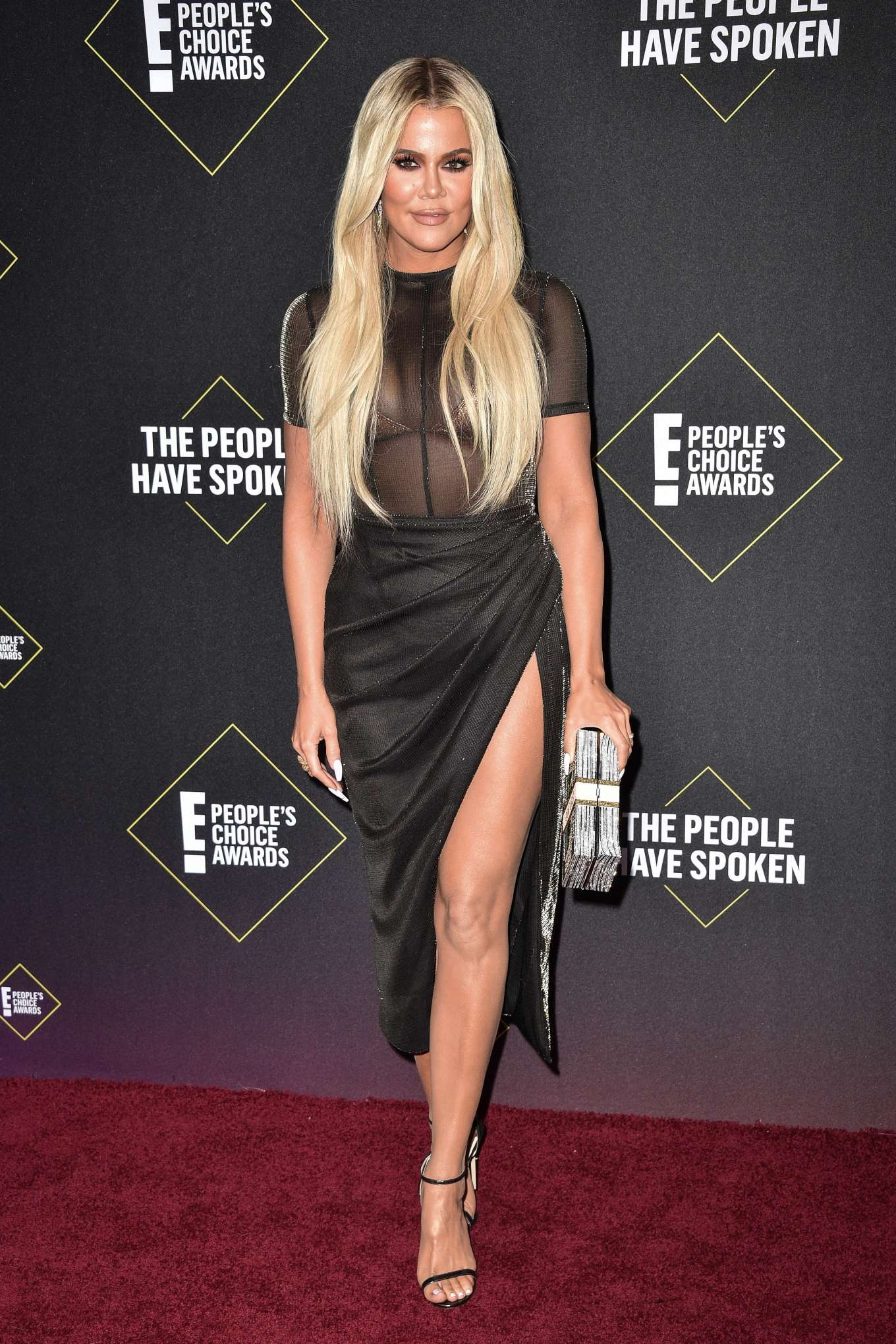 Khloe Kardashian donning a Sheer black tee with a sheer fabric, short sleeves, striped and a crew neck