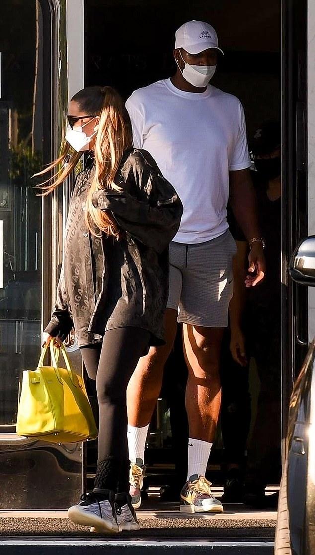 Khloe Kardashian donning white lace-up sneakers