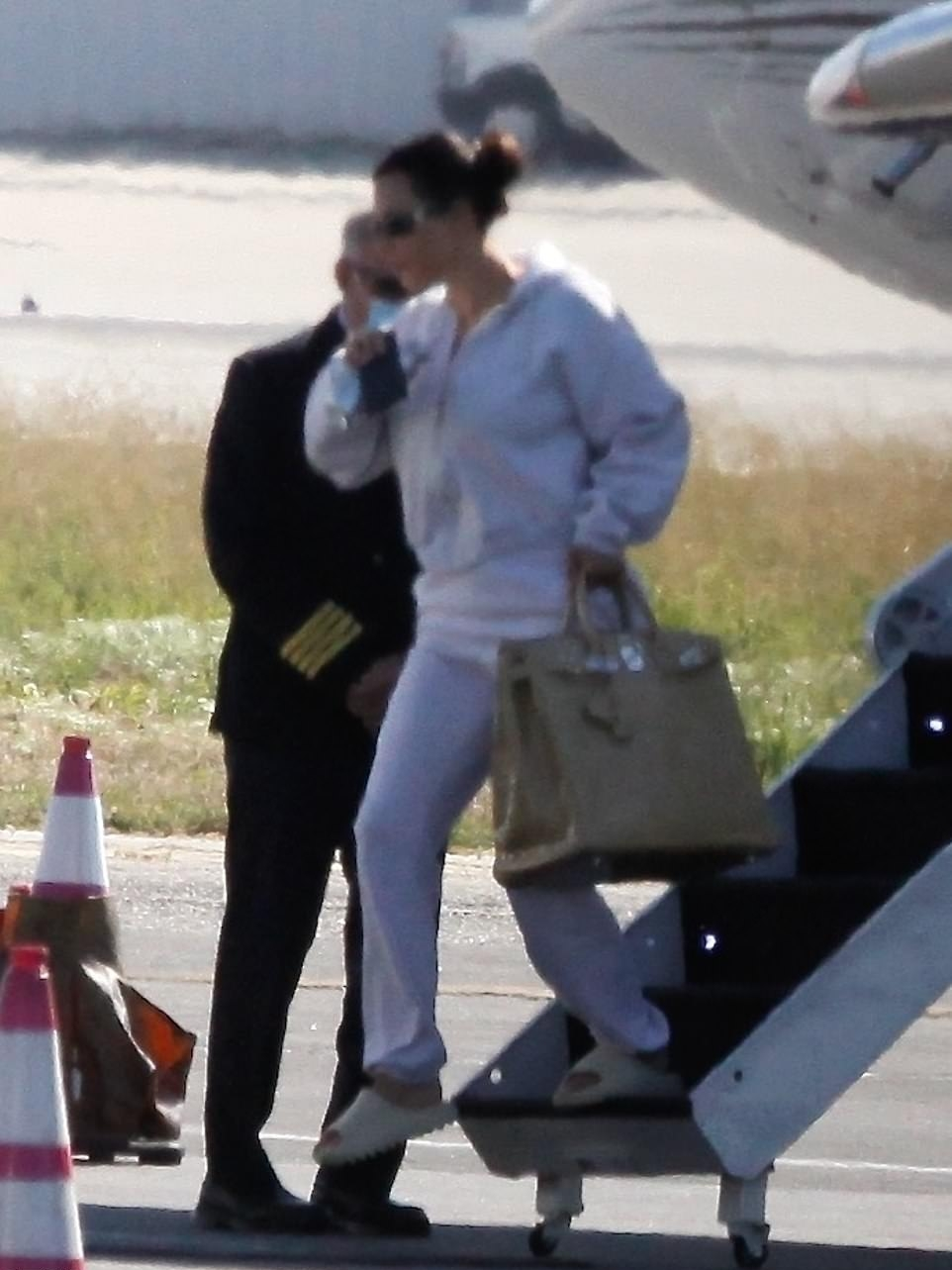 Kim Kardashian donning off white Adidas x Yeezy open toe sandals with chunky sole