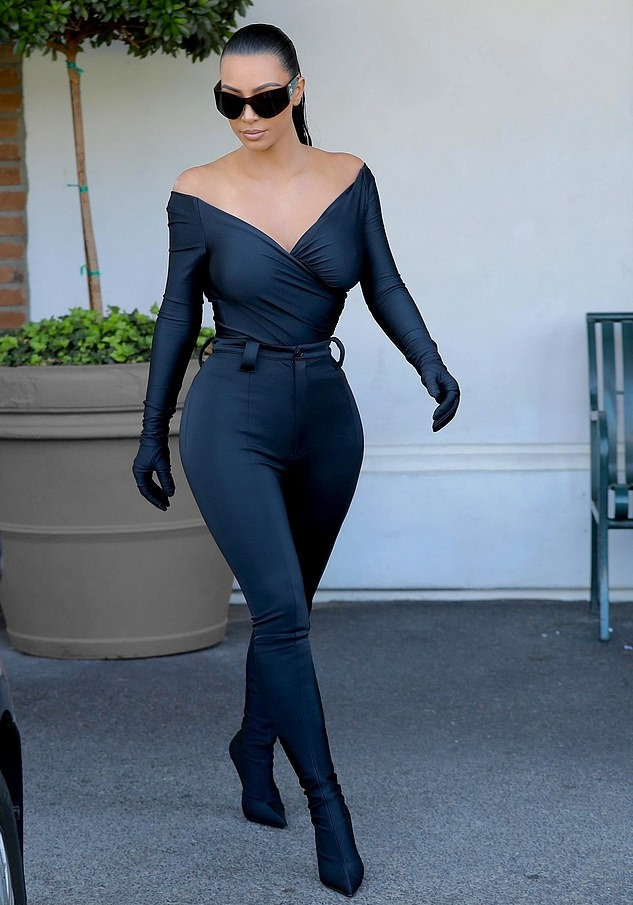 Kim Kardashian wearing a figure hugging plunging top that hugged her body in all the right places while out and about in California