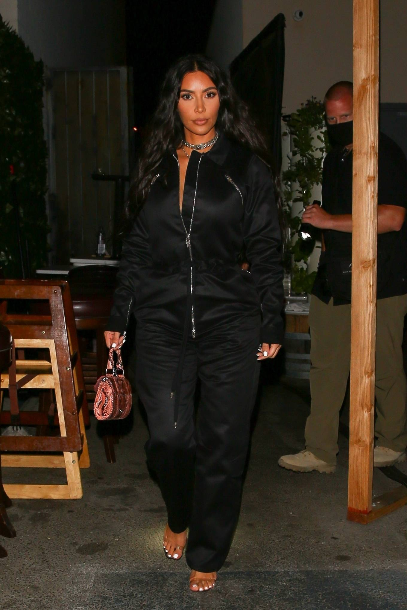 Kim Kardashian donning a relaxed fit black jumpsuit with a denim fabric, full sleeves, drawstring and cinched waist