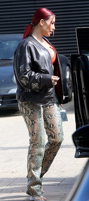 Kim Kardashian, black  jacket, faux leather, completely see-through sandals, Neon orange crop top, welted pockets, hip length, extra long sleeves, oversized, silver purse, beige Gucci trousers, button front