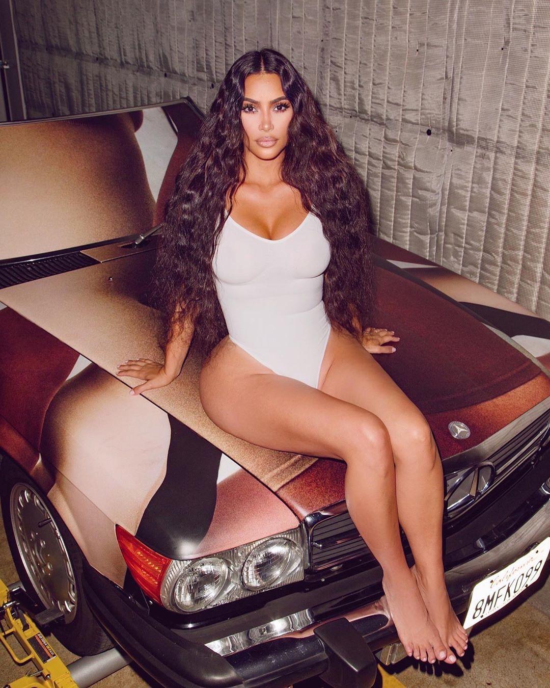 Kim Kardashian rocking a Plunging white Skims bodysuit with a V-neck and spaghetti straps