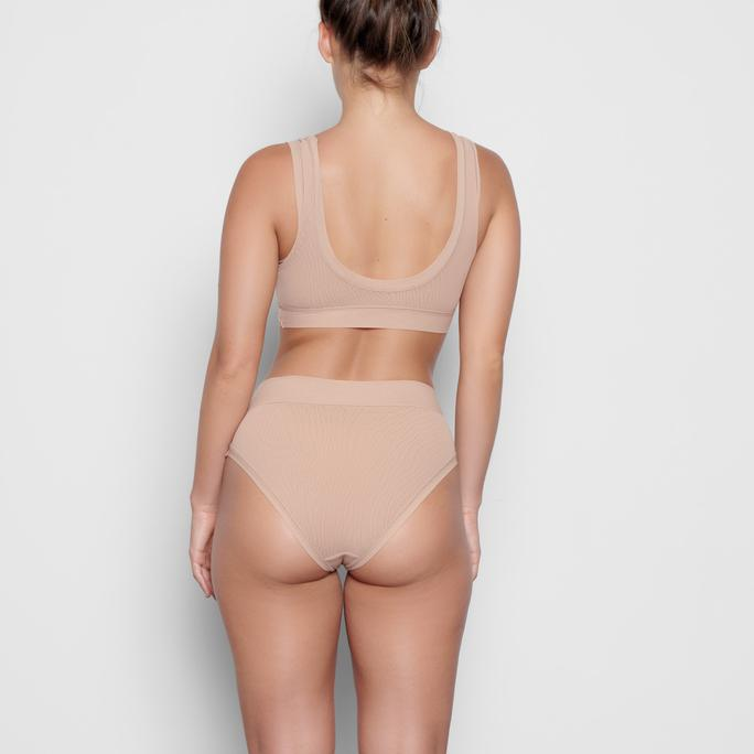 Kim Kardashian donning Clay luxe loungewear Skims mesh brief with a mesh material