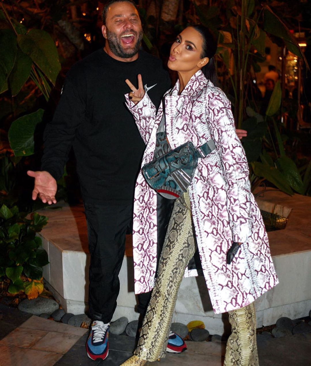 Kim Kardashian donning a Oversized grey button front snakeskin coat with a snakeskin fabric, extra long sleeves, wide collar and button front