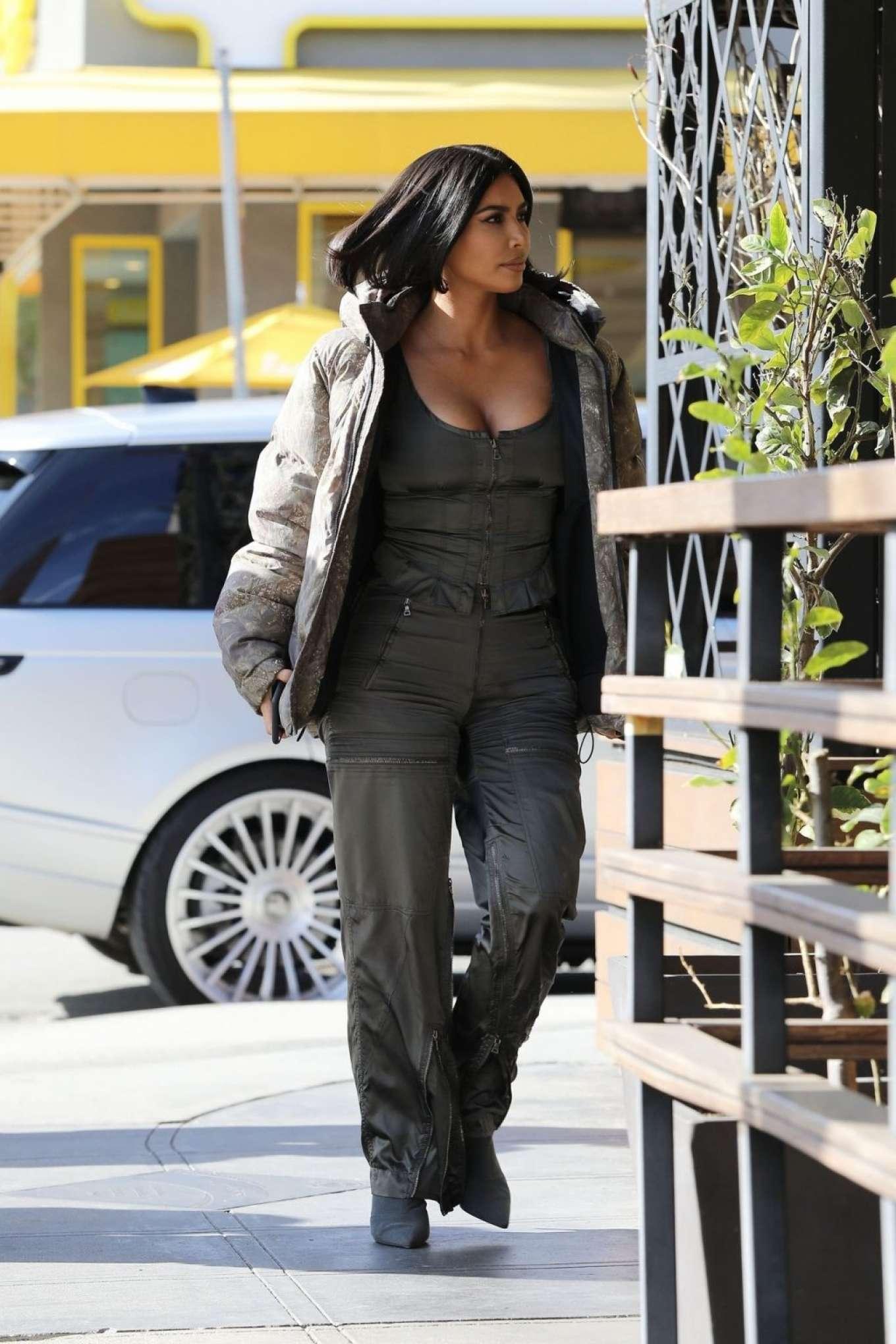 Kim Kardashian donning Dark grey straight fit pants with side pockets