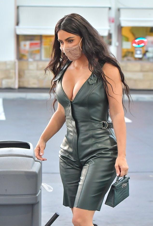 Kim Kardashian donning pointy balsam green suede knee high boots by Yeezy with high heel