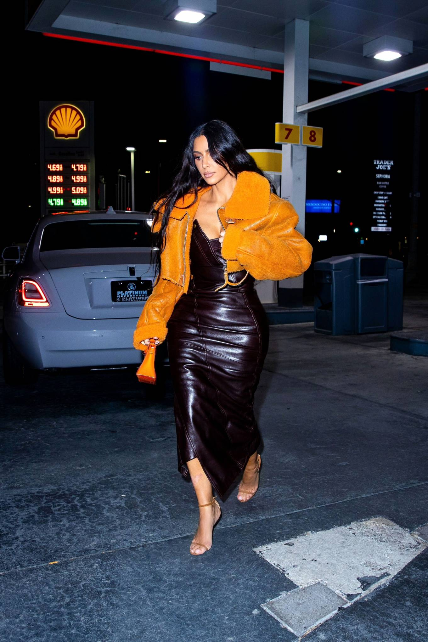 Kim Kardashian donning pointed orange open toe sandals with high heel