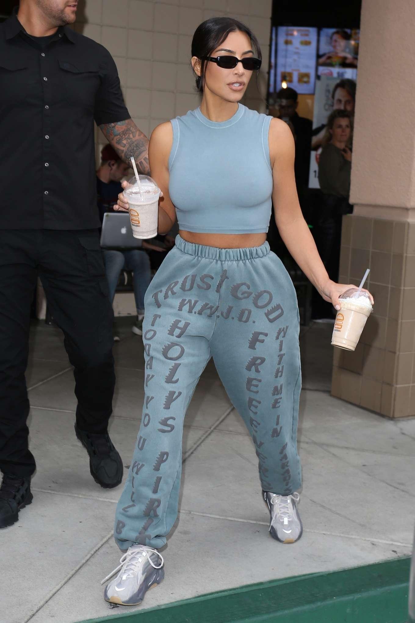 Kim Kardashian rocking off white grey lace-up sneakers
