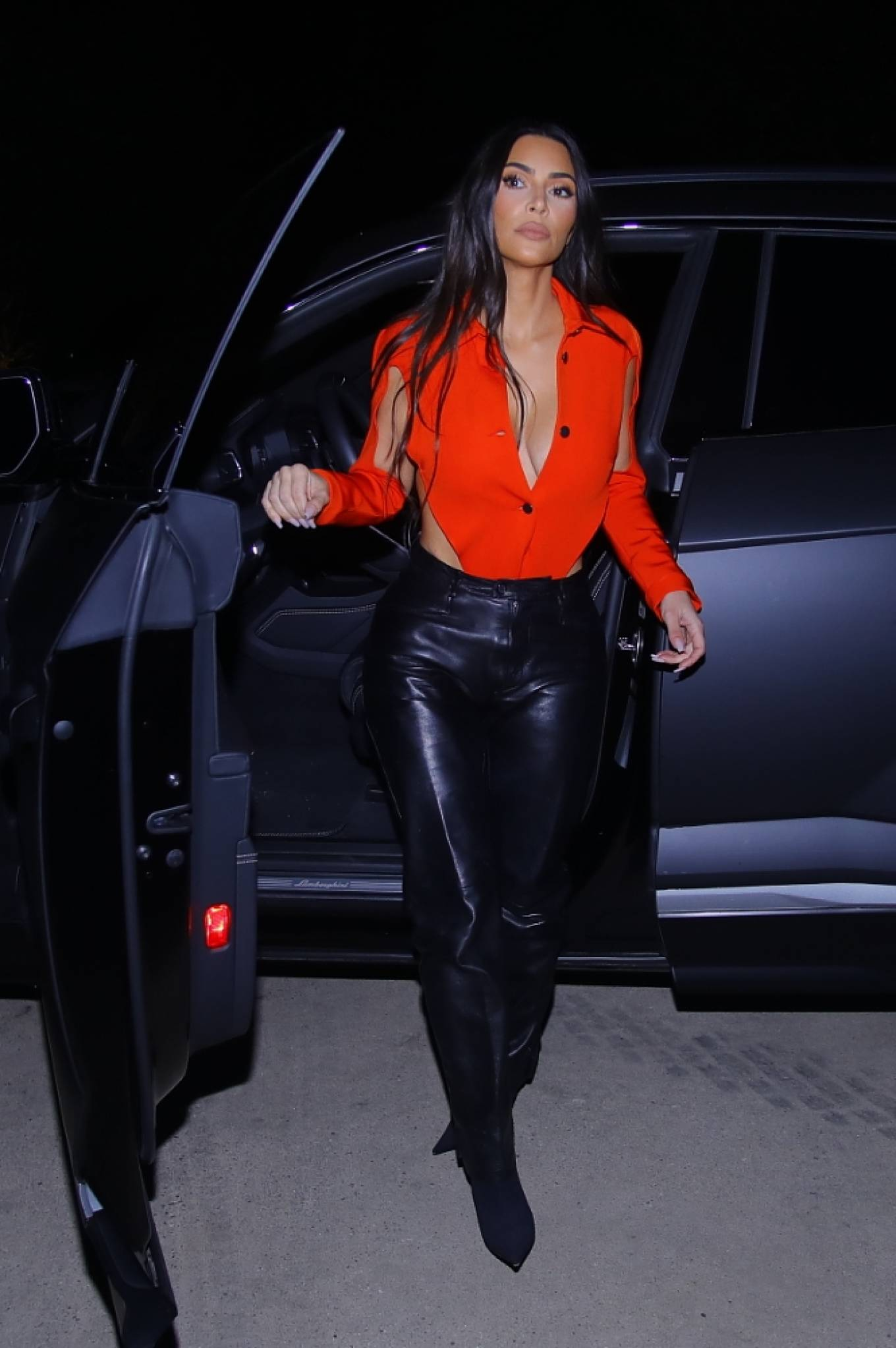 Kim Kardashian donning a very low neck red bodysuit with long sleeves and large cut out details on the hands and waist