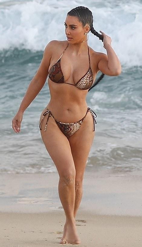 Kim Kardashian sizzled in a Plunging brown bikini top with spaghetti straps