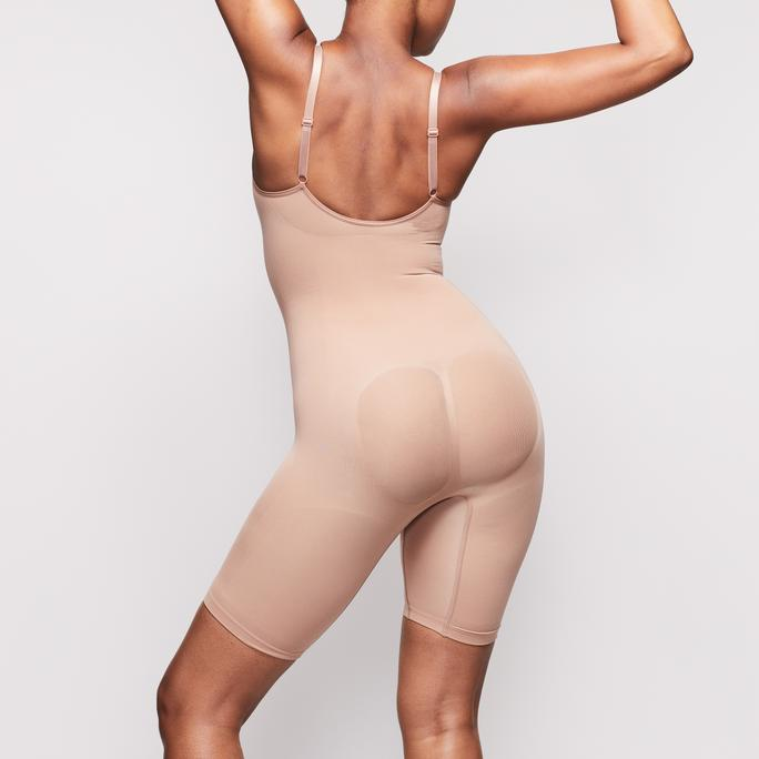 Kim Kardashian donning a Plunging nude Skims bodysuit with a stretch fabric, thin shoulder strap and a scoop neck