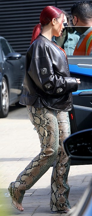 Kim Kardashian donning a oversized black button front faux leather jacket with extra long sleeves and welted pockets