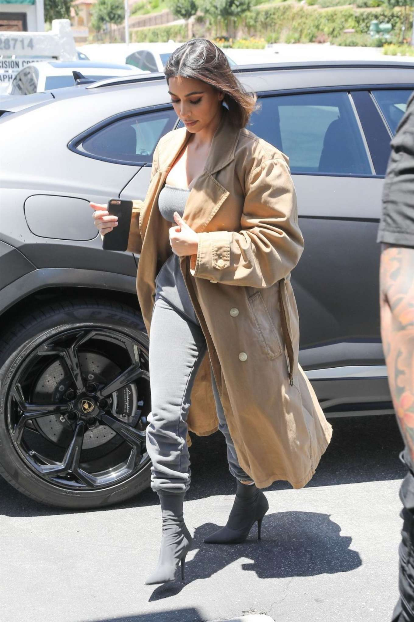 Kim Kardashian rocking a Oversized beige button front suede trench coat with a suede fabric, extra long sleeves, peak lapel collar and button front