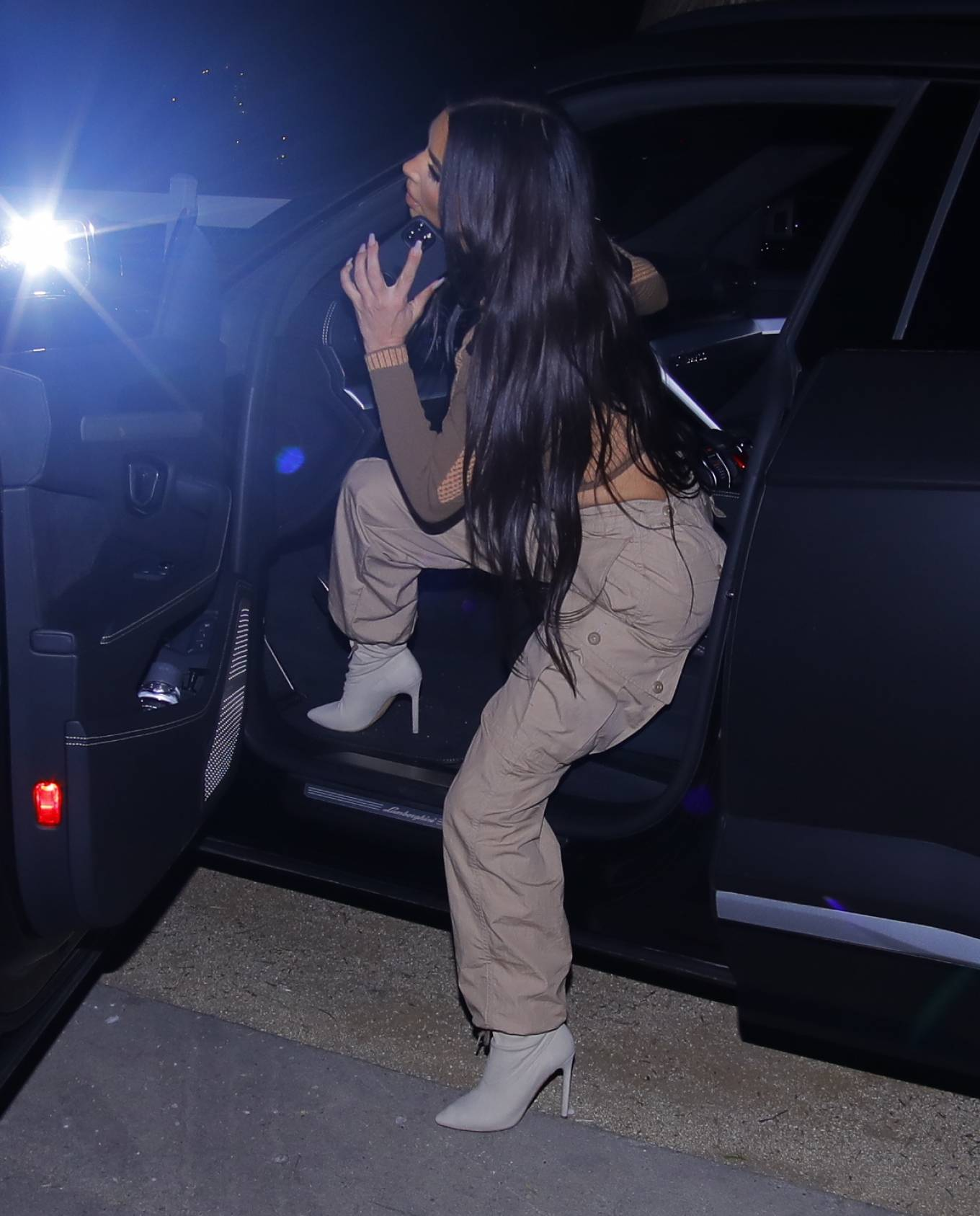 Kim Kardashian donning pointed grey Yeezy ankle boots with stiletto heels