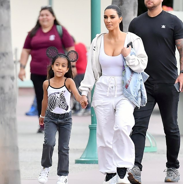 Kim Kardashian, grey tank top, braless, oversized khakhi jacket, grey high top sneakers, showcase, straps, scoop neck, tucked in, figure hugging. Kim Kardashian donning a Figure hugging grey tank top with a scoop neck and straps