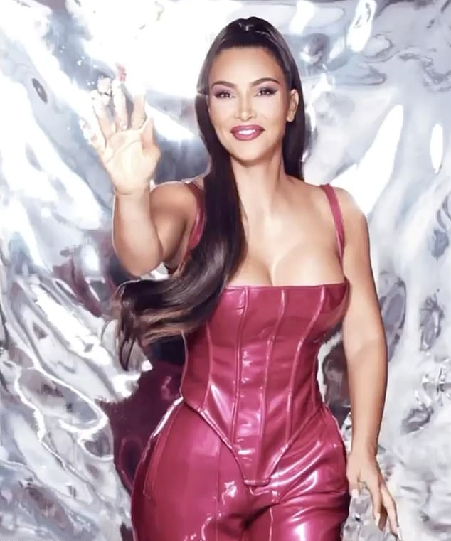 Kim Kardashian donning a plunging shiny magenta crop top with a leather fabric, thin shoulder strap, asymmetric design and asymmetric hem