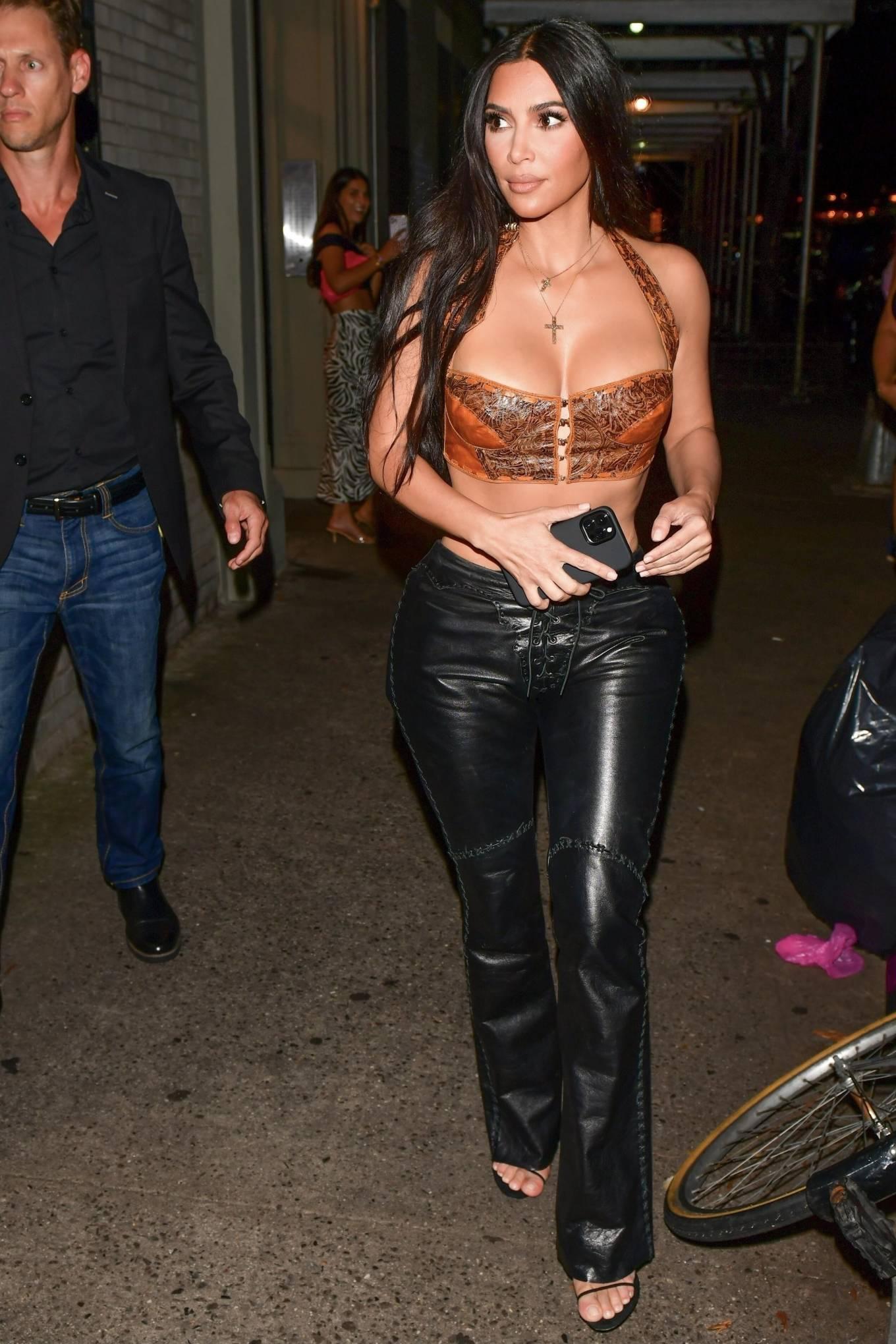 Kim Kardashian, black sandals, black hand bag, black pants, unusual shaped, open toe. Kim Kardashian rocking black open toe sandals