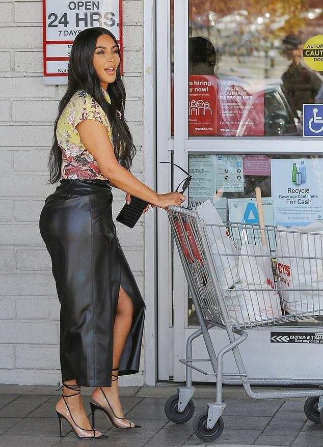 Kim Kardashian rocking narrow black PVC crisscross tie sandals with ice pick heel