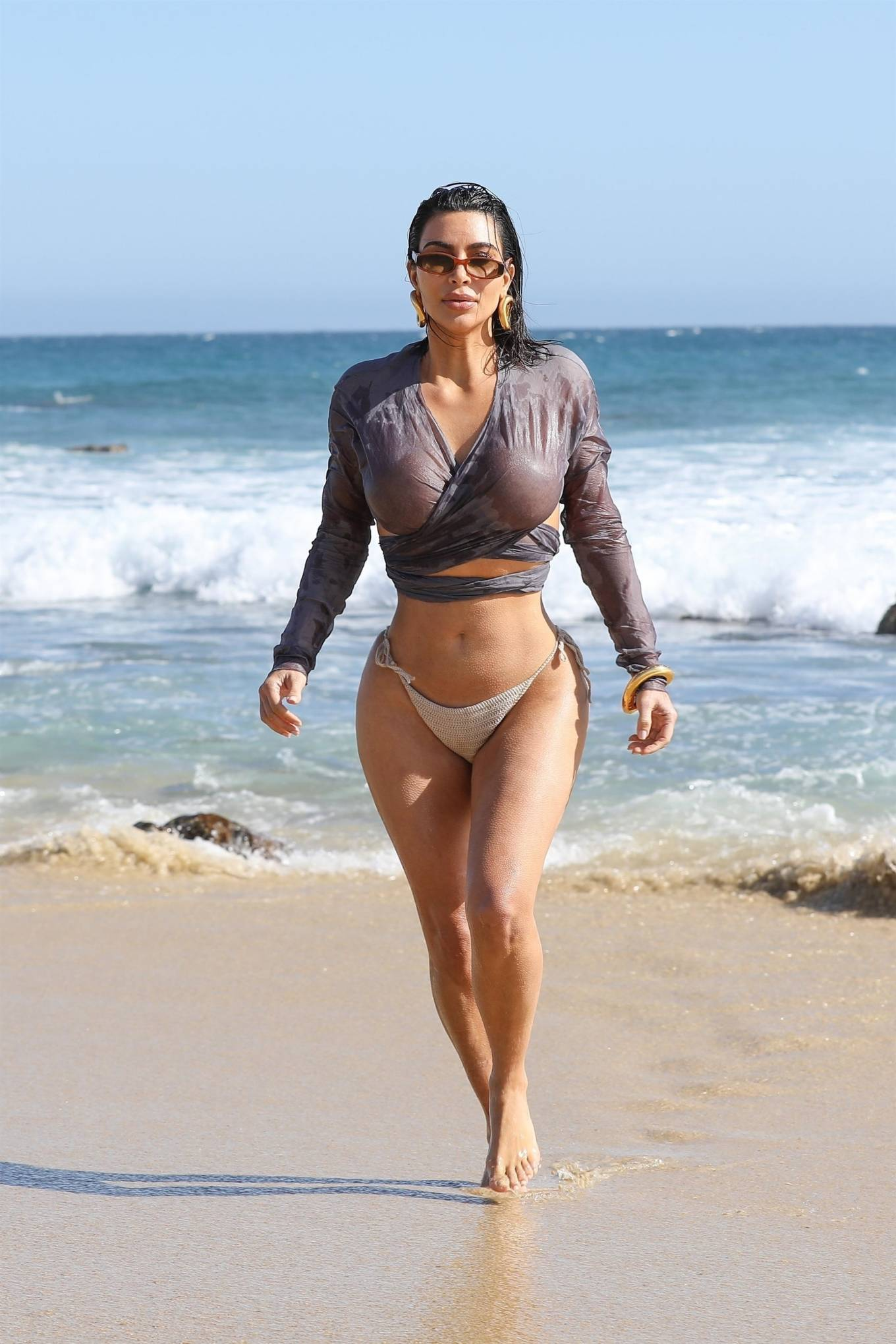 Kim Kardashian donning a see-through grey crop top with full sleeves and a V-neck