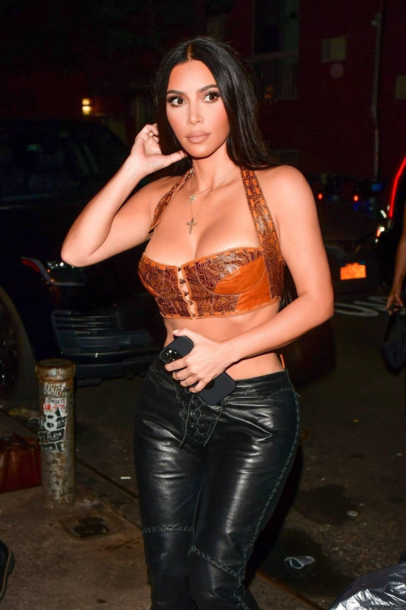 Kim Kardashian, black sandals, black pants, black hand bag, unusual shaped, open toe. Kim Kardashian rocking black open toe sandals