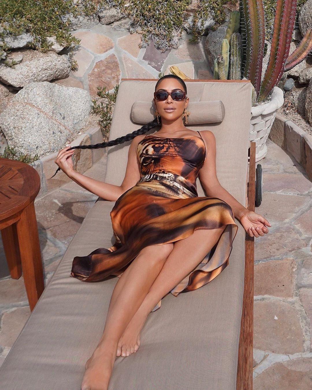 Kim Kardashian wearing a Slinky tan printed maxi dress with a satin fabric, a scoop neck and spaghetti straps