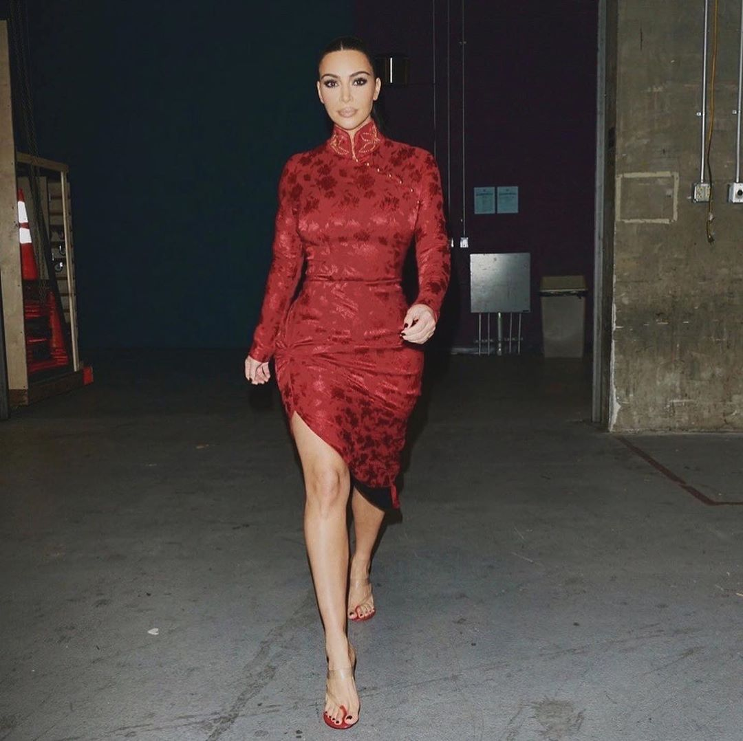 Kim Kardashian donning a Figure hugging deep red printed midi dress with a satin fabric, full sleeves, ruched, a high neck and asymmetric hem