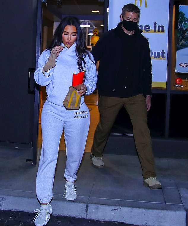 Kim Kardashian rocking round white Adidas x Yeezy lace-up sneakers with chunky heel