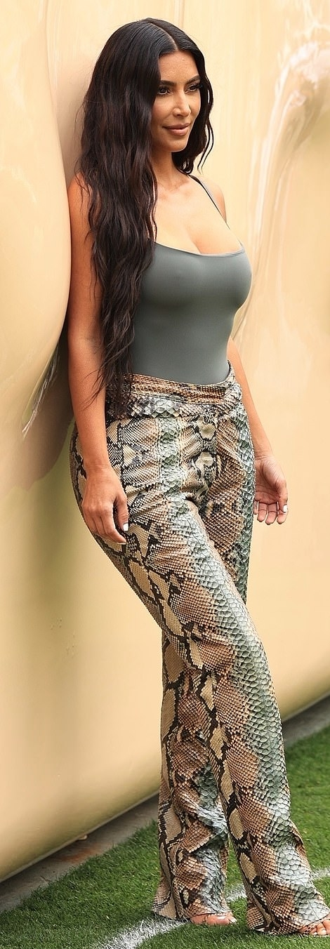 Kim Kardashian donning flare leather animal print trousers with mid rise